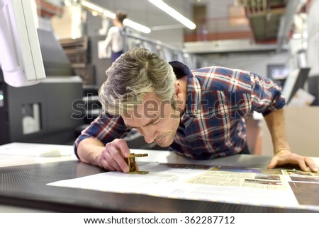 Man working on printing machine in print factory