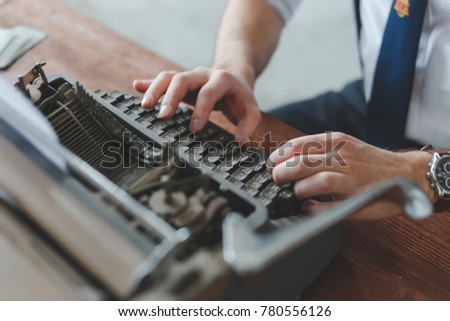 Man working on retro typewriter at desk in parlor room #780556126