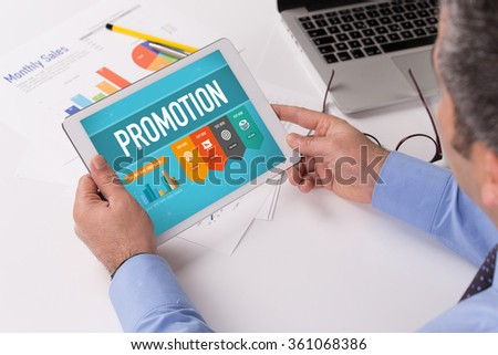 Man working on tablet with PROMOTION on a screen