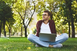 Man working outdoors on computer. Preparing for exams, sitting on the grass at university campus park. Technology, communication, education and remote working concept, copy space