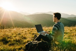 Man working outdoors with laptop sitting in mountains. Concept of remote work or freelancer lifestyle. Cellular network broadband coverage. internet 5G. Hiker tourist enjoying valley view sunset.