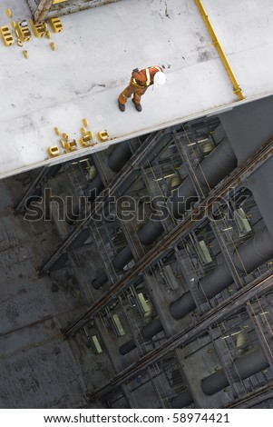 man working over precipice aboard container ship during cargo operation in port terminal