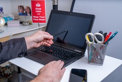 Man working remotely from home on a Laptop computer with VPN network internet access to the business during the Covid 19 Pandemic