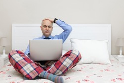 Man working with a laptop on a bed dressed in a shirt and tie and pajama pants and with his hand over his head with a worried expression. Teleworking concept