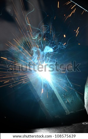Man working with arc welding equipment/Arc Welder/Blue light from arc welding and a man with protective gear