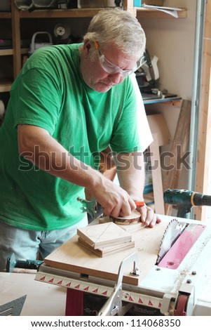Man working with table saw, screwdriver and other tools - stock photo