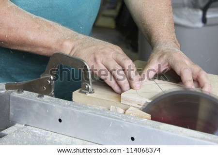 Man working with table saw, screwdriver and other tools