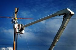Man working worker on power lines in crane bucket high in the air dangerous work