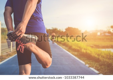 Man workout and wellness concept : The asian runner warm up his body before start running on road in the park. Shot in morning time, sunlight and warm effect with copy space for text or design
