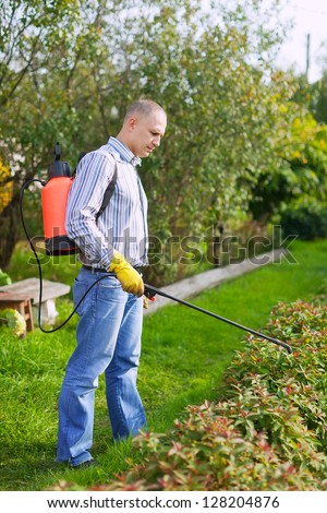 Man works with garden spray  in the yard