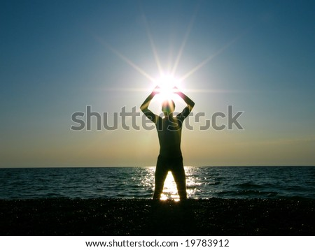 man worshiping the sun at dawn