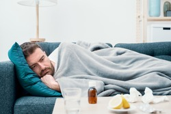 Man wrapped in plaid lying on the sofa feeling sick illness at home
