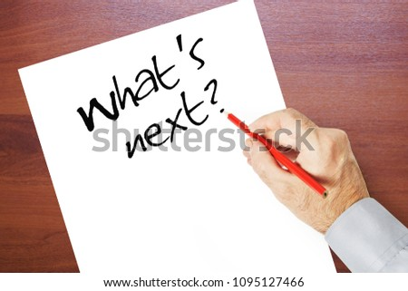 Man writes on a paper sheet What is next. Concept of thinking and self knowledge