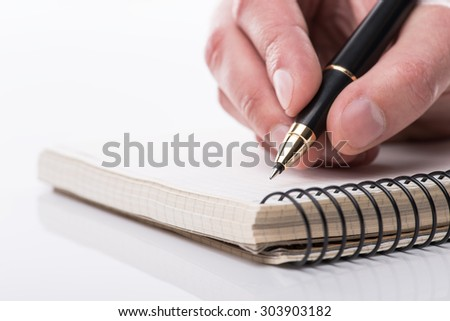 Man writing a note with black ball pen in his hand over the white background, isolated