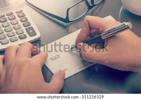 Man writing a payment check at the table with calculator and glasses #311226329