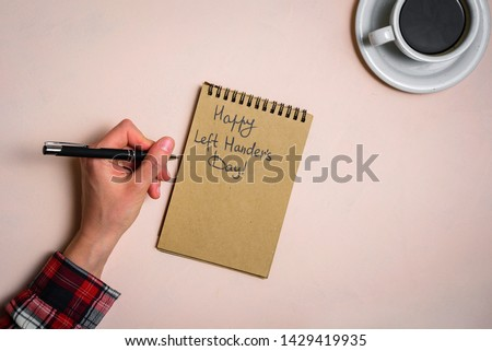 Man writing by left hand. Left hander day concept. Working place of lefty #1429419935