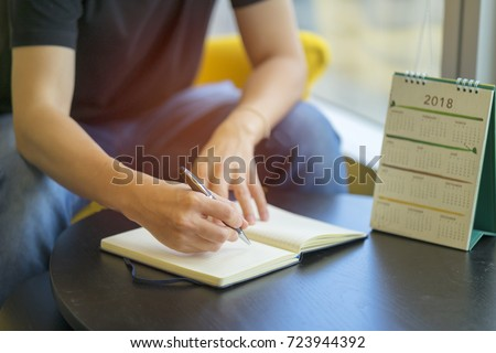 Man writing diary or notebook with calendar 2018 on table. Organize planing business event, schedule to support business organizer and booking timeline for payment reminder. Calendar 2018 concept