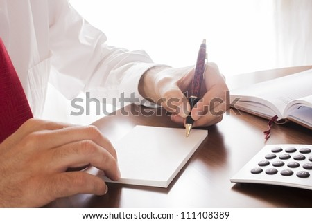 man writing in the office table