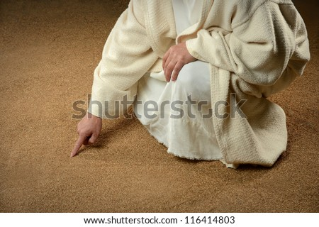 Man writing in the sand with finger