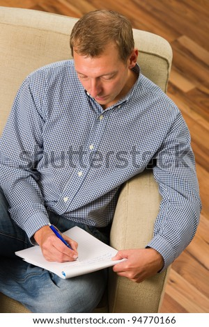 Man writing letter on the armchair.