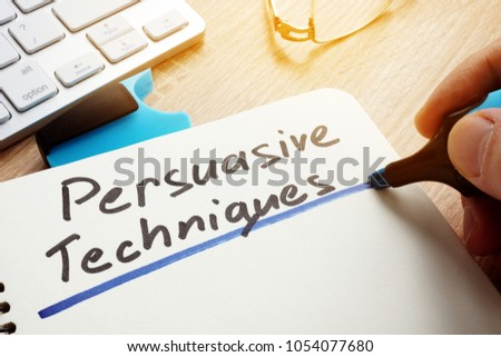 Man writing Persuasive Techniques in a note. Foto stock ©
