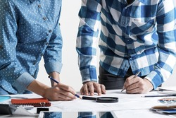 Man writing with pen on technical drawing. Creative team of designers together working with construction blueprint. Thorough study and approval of design project. Architecture studio concept.
