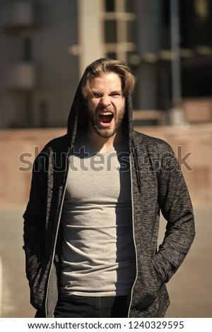 Man yawning with hood on head and grey tshirt on sunny morning outdoors on streetscape. Sportswear and fashion. Sportswear and fashion. Leisure, sporty style, active, urban, lifestyle concept