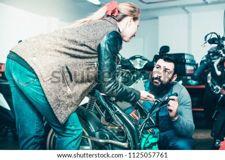 Man 20-29 years old is helping female client to fix bike in motorcycle workshop.