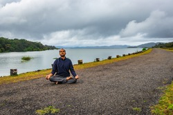 man young isolated meditating at river edge with the pristine nature image is taken at supa dam dandeli karnataka india. it is showing the breathtaking beauty of nature at south india.
