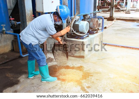 Manage Spills, leaks and disposal of chemicals leaking. Asian man wearing safety equipments, Rubber gloves and face-mask. Sand or dry soil scattered over the chemical leak. - Safety concept. #662039416