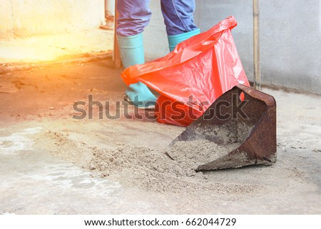 Manage Spills, leaks and disposal of chemicals leaking. Asian man wearing safety equipments. Sand or dry soil on the dirty dustpan, chemical leak with red plastic container. - Safety concept. #662044729