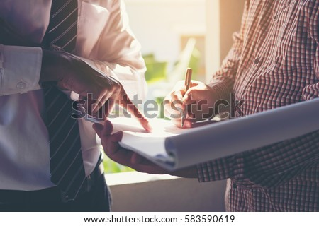 Management consulting with engineers working at construction site and holding blueprint in his hand for management business plan.