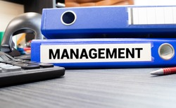 Management words on labels with document binders, graphs and business reports