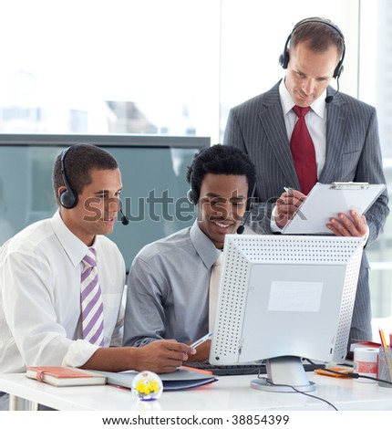 Manager and businessmen working in call center with a headset on