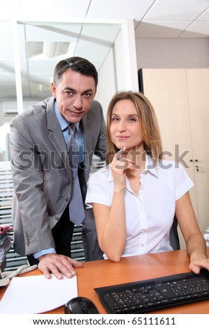 Manager and employee in front of computer in the office