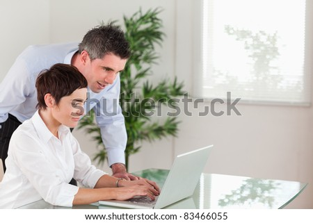 Manager and his secretary working with a laptop in an office