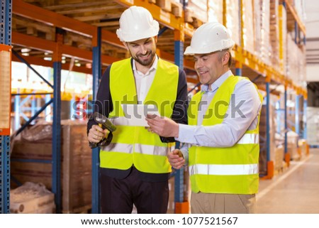 Manager and subordinate. Positive nice man holding a tablet while showing it to his subordinate