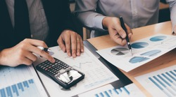 Manager calculates about the company finances by pressing on the calculator on the table with the employee explaining the summary report of the company cost at the office.