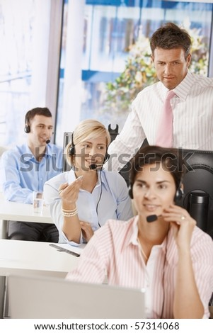 Manager checking customer service operators in office.?