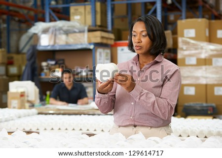 Manager Checking Goods On Production Line