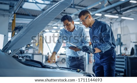 Manager Checks Diagnostics on a Tablet Computer and Explains the Engine Breakdown to a Mechanic. Car Service Employees Inspect Car's Engine Bay with a LED Lamp. Modern Clean Workshop. Photo stock ©