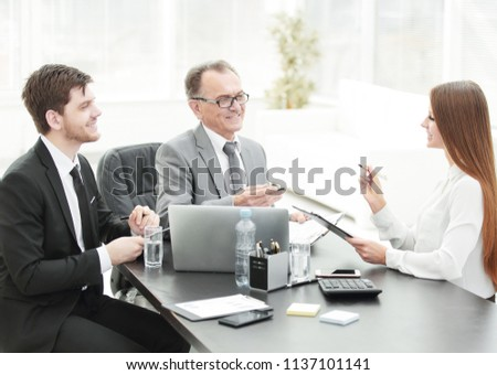 Manager discussing work issues with his assistants behind a Desk #1137101141