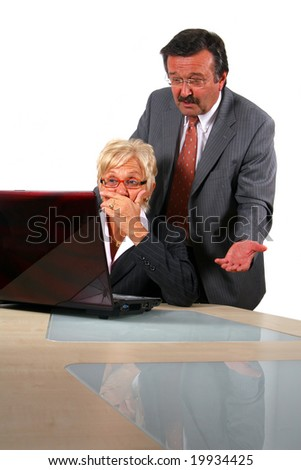 Manager Explains To Secretary A business woman and a man in front of a laptop on a desk. The man explains something to the woman. She is shocked. Isolated over white.