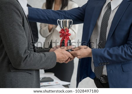 Manager giving employee the trophy award for success in business.