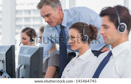 Manager Helping Call Centre Agent On A Computer