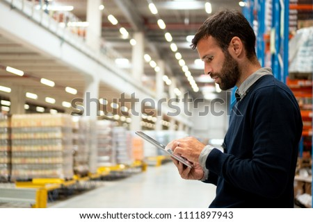 Manager holding digital tablet in warehouse #1111897943