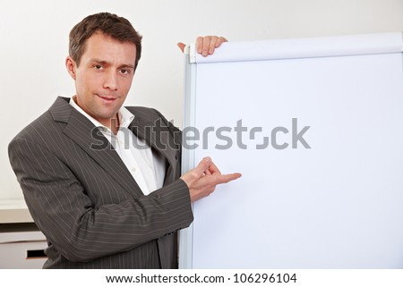 Manager in office pointing with index finger to empty flipchart