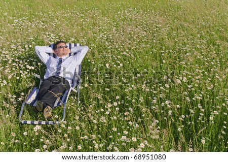 Manager in the Open and is relaxed on a striped deck chair on a lazy meadow