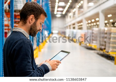 Manager in warehouse holding digital tablet #1138603847