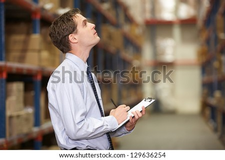 Manager In Warehouse With Clipboard